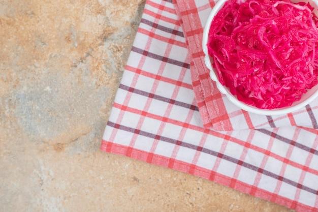 Rode zuurkoolsalade in witte kom met tafelkleed