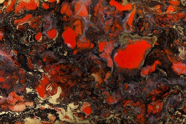 Rode, zwarte en gouden verf vloeibare achtergrond. abstracte marmeren textuur.