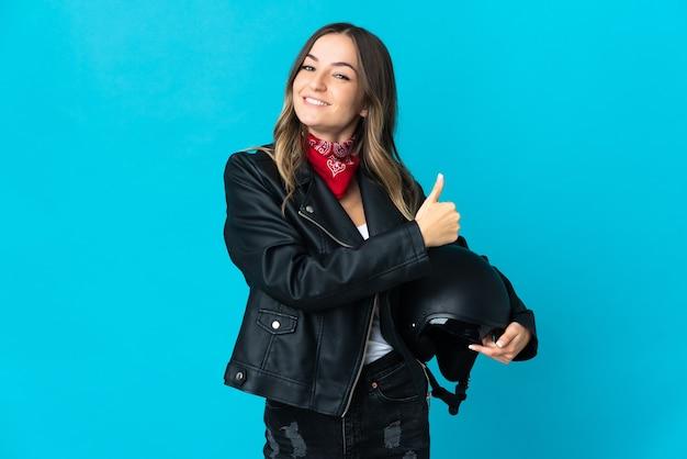 Roemeense vrouw die een motorhelm houdt die op blauwe muur wordt geïsoleerd die een duim omhoog gebaar geeft