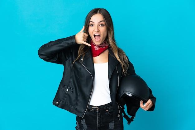 Roemeense vrouw die een motorhelm houdt die op blauwe muur wordt geïsoleerd die telefoongebaar maakt. bel me terug teken