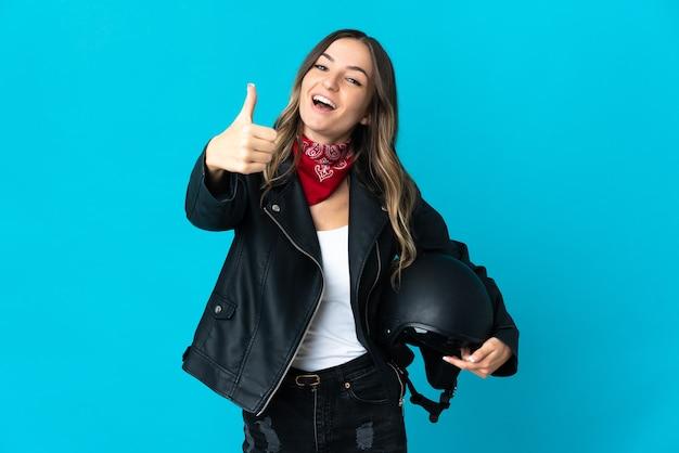 Roemeense vrouw met een motorhelm geïsoleerd op blauwe muur met duimen omhoog omdat er iets goeds is gebeurd