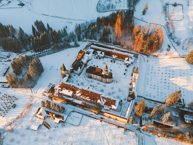 Roemenië / suceava- 7 / januari / 2020 luchtfoto van drone van putna-klooster in de winter bij zonsondergang in roemenië