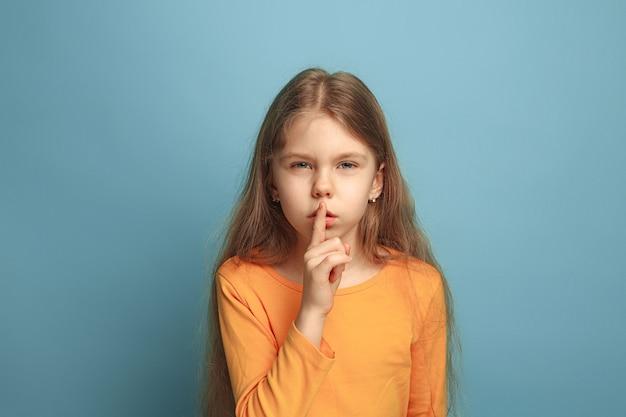 Roep om stilte. verrast tienermeisje op een blauwe studioachtergrond. gezichtsuitdrukkingen en mensen emoties concept.