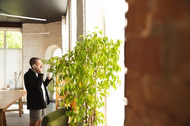 Roeping. jonge man zonder broek maar in jas aan het werk op een computer, laptop. extern kantoor tijdens coronavirus, leuk en comfortabel in onderbroek. isolatie, quarantaine, humor, bedrijfsconcept.