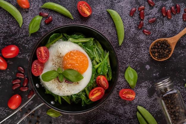 Roer boerenkool en gebakken ei in een pan.