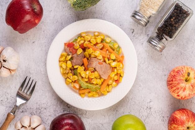 Roer de mais en wortelen, leg het varkensvlees op het bord op het houten bord.