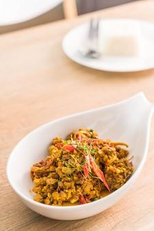 Roer gebakken gehakt varkensvlees met hete gele curry pasta