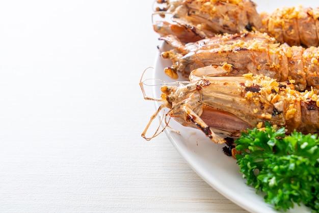 Roer gebakken mantis garnalen met knoflook op witte plaat