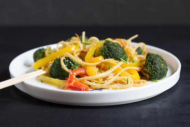 Roerbak chinese noedels met groenten op de zwarte tafel, gekookt in de wok
