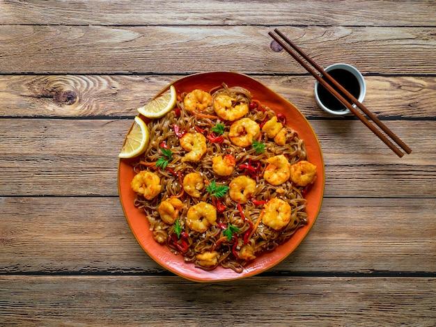 Roerbak de noedels met gebakken garnalen, groenten en sojasaus