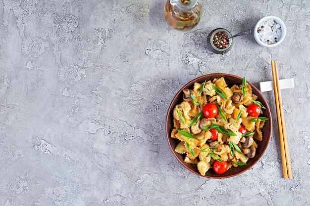 Roerbak de pasta met groenten, bloemkool en champignons. bovenaanzicht
