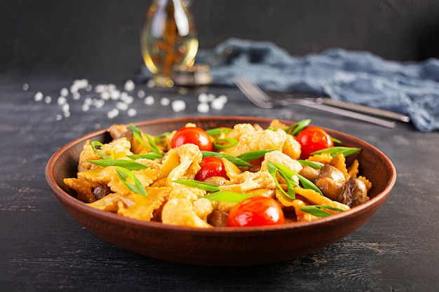 Roerbak de pasta met groenten, bloemkool en champignons