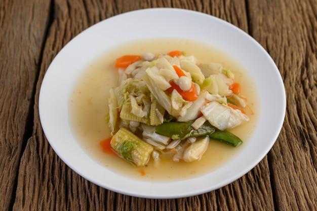 Roerbak gemengde groenten op een witte plaat op een houten tafel.