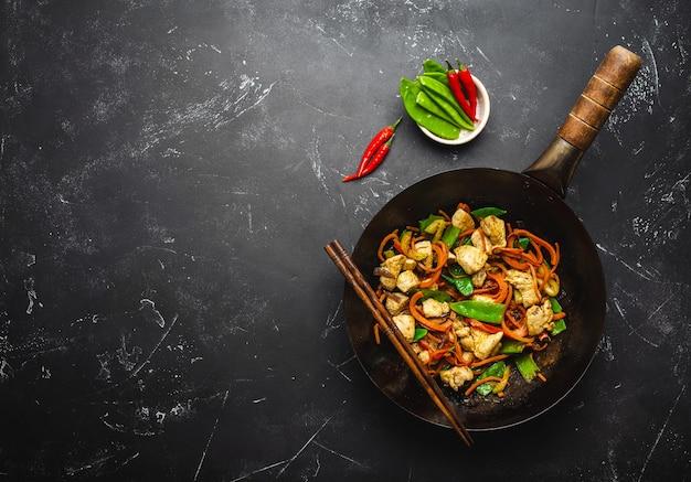 Roerbak kip met groenten in oude rustieke wokpan, eetstokjes op zwarte stenen achtergrond, close-up, bovenaanzicht. traditionele aziatische/thaise maaltijd, ruimte voor tekst