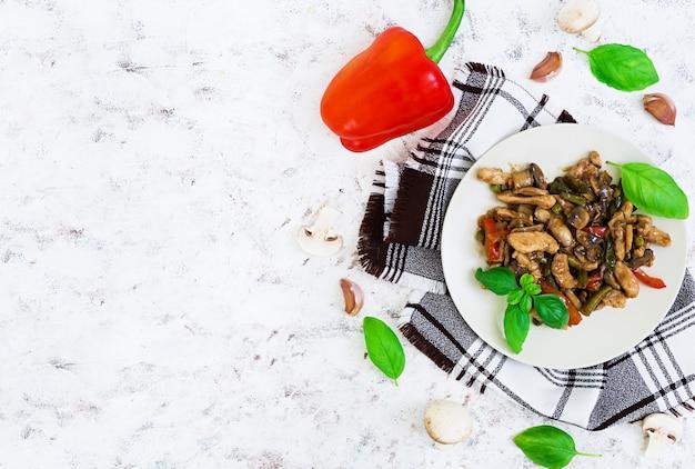 Roerbak kip met paprika en erwten op wit