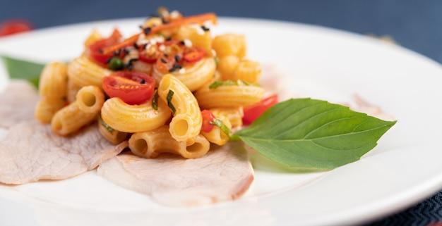 Roerbak macaroni op varkensvlees bovenop in een witte plaat.