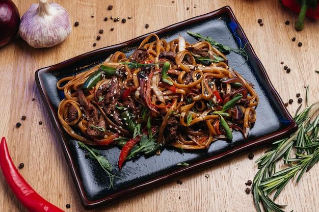 Roerbak noedels met groenten en rundvlees in zwarte plaat houten achtergrond close-up
