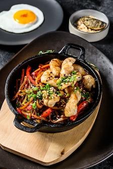 Roerbak noedels met groenten, kip. woknoedels. zwarte achtergrond. bovenaanzicht