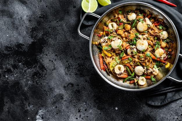 Roerbak noedels met inktvis en groenten in een wokpan. kopieer de ruimte