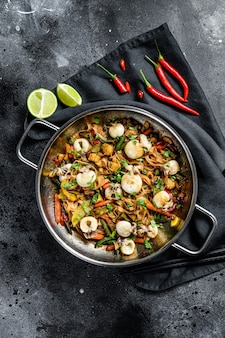 Roerbak noedels met zeevruchten en groenten in een wokpan