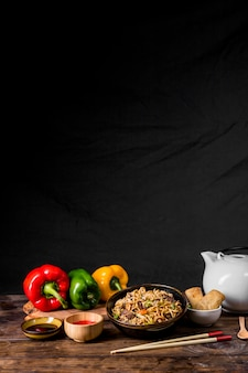 Roerbak noodles met groenten en kip met paprika; sauzen en loempia op bureau tegen zwarte achtergrond