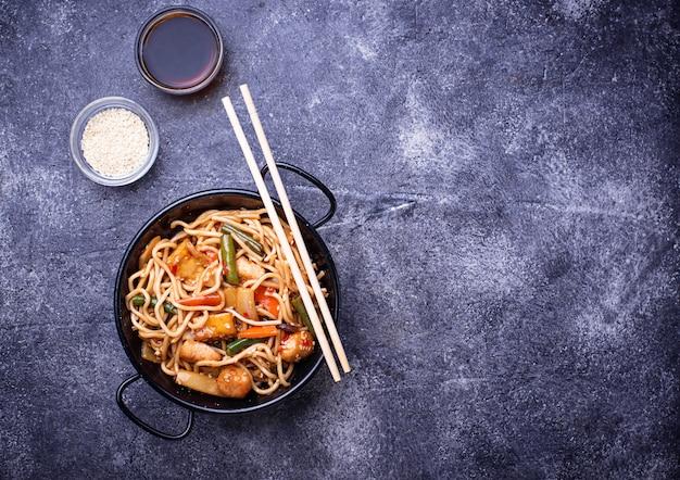 Roerbak noodles met kip, tofu en groente.