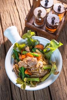 Roerbak sojasaus met boerenkool, voeg varkensvlees toe, doe wortelen, voeg eieren toe en heerlijk, met garnering, doe in een mooie terracotakop