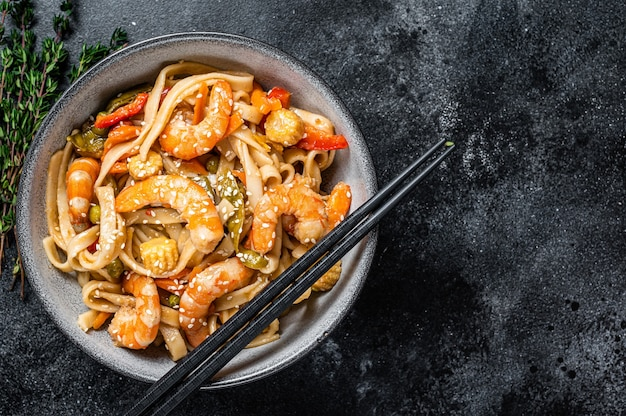 Roerbak udon zeevruchtennoedels met garnalen in een kom