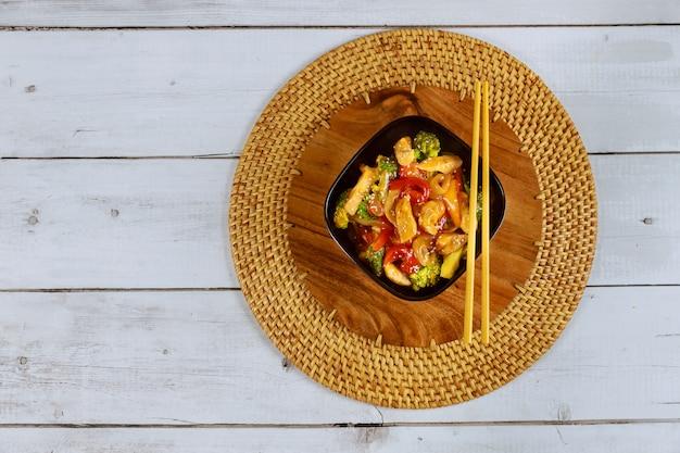 Roerbak vlees met groente in zwarte kom met eetstokje