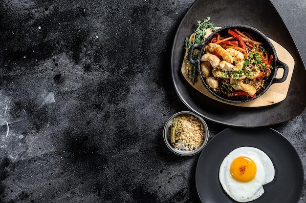 Roerbaknoedels met groenten, kip. wok noedels. zwarte achtergrond
