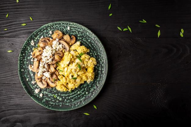 Roerei als ontbijt. gebakken ei met champignons en kwark op plaat, bovenaanzicht, kopie ruimte.