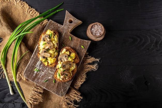 Roerei en champignons op volkoren toast. zelfgemaakte maaltijd, bovenaanzicht, plat leggen.