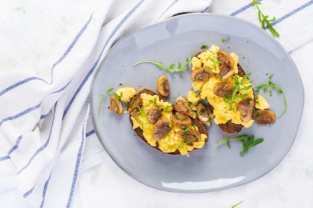 Roerei en gebakken champignons op brood