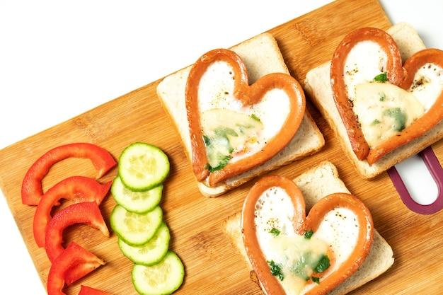 Roerei in worst, hartvormige worst, hart, ontbijt, bovenaanzicht op schoolbord