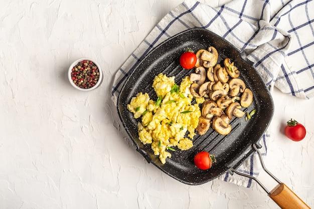 Roerei met champignons, tomaten in de pan. bieslook zelfgemaakte maaltijd, bovenaanzicht, plat leggen.