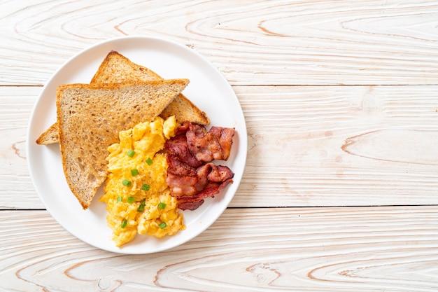 Roerei met geroosterd brood en spek als ontbijt