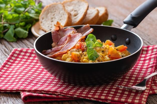 Roerei met gesneden tomaat, spekgrill op pan en brood, huisgemaakt ontbijt.