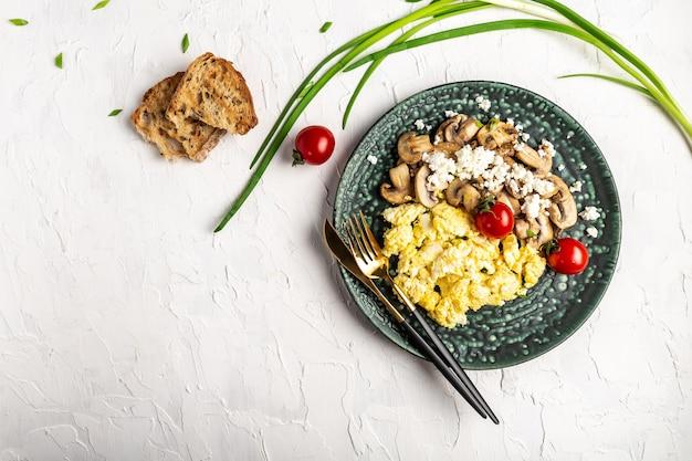 Roerei met toast, champignons, ui en tomaten.