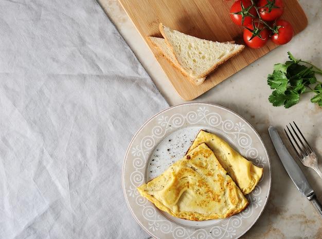 Roerei op een bord, peterselie, tomaten, toast en textiel servet