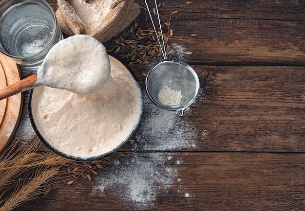 Roeren met een lepel actieve startercultuur. ingrediënten voor het maken van brood. getinte culinaire achtergrond met kopie ruimte.