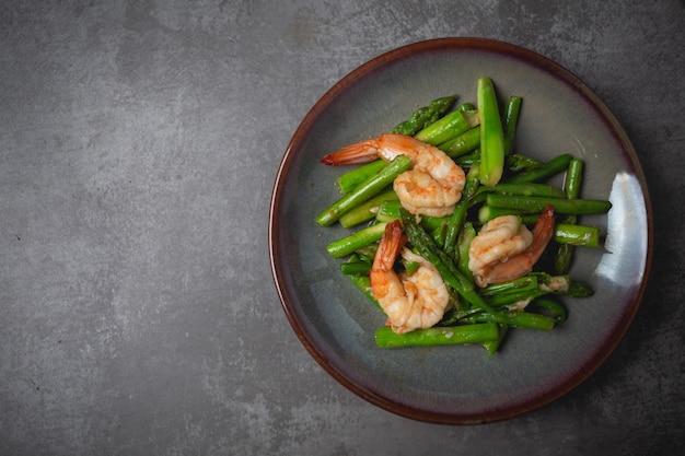 Roergebakken asperges en garnalen op tafel.