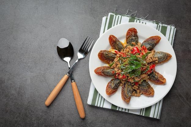 Roergebakken basilicum met pittig ei uit de eeuw geserveerd met gestoomde rijst en chili vissaus, thais eten.