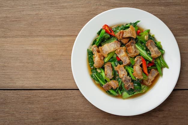Roergebakken boerenkool, pittig krokant varkensvlees op houten tafel thais eten concept.
