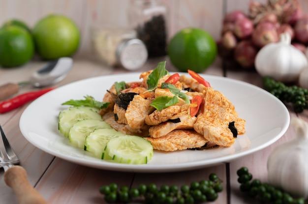 Roergebakken chilipasta met kip in witte platen op een houten vloer.