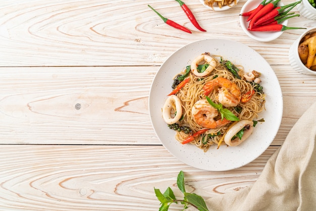 Roergebakken chinese noedels met basilicum, chili, garnalen en inktvis, aziatisch eten