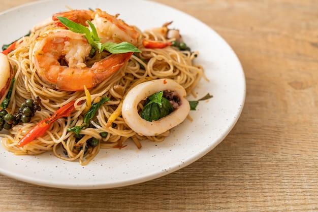Roergebakken chinese noedels met basilicum, chili, garnalen en inktvis - aziatisch eten