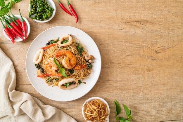 Roergebakken chinese noedels met basilicum, chili, garnalen en inktvis - aziatische eetstijl