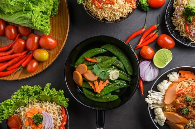Roergebakken erwten in een koekenpan en noedels kruidig in de kom met ingrediënten op zwarte cementoppervlakte.