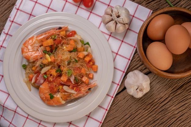 Roergebakken garnalen met glasnoedels in een witte plaat op een doek met eieren en knoflook.