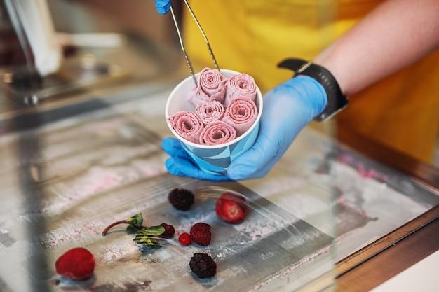 Roergebakken ijs rolt bij vriespan. met de hand gemaakt gerold roomijsdessert op koude plaat. gebakken ijsmachine met stalen gekoelde pan.